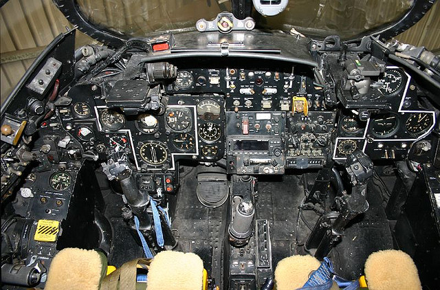 view of a historical airplane cockpit with many mechanical buttons and displays